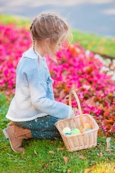 Dziewczyna patrzeje dla wielkanocnych jajek w trawie przy wielkanocą