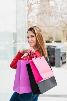 Dziewczyna patrzeje kamerę podczas gdy trzymający torba na zakupy