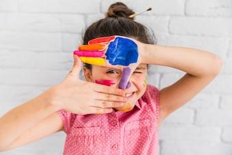 Dziewczyna patrzeje przez palec ramy z farbami na palmie przeciw białemu ściana z cegieł