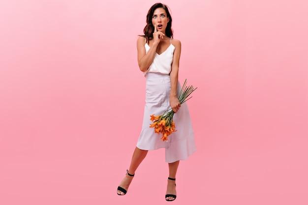 Dziewczyna patrzy na aparat ze zdziwieniem i trzyma pomarańczowe kwiaty. ładny zaskoczony kobieta w długiej spódnicy światło pozowanie w czarne buty.