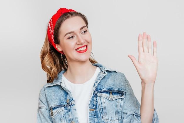 Dziewczyna patrzy na jej lewą rękę na białym tle na tle szarej ścianie
