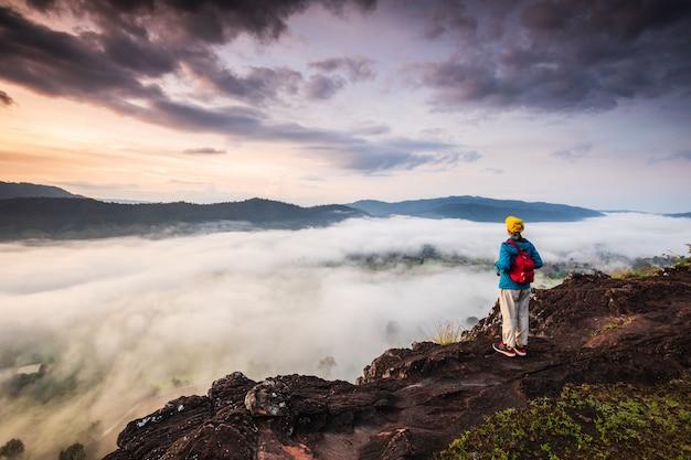 Dziewczyna patrzy na morze mgły na wysokiej górze.