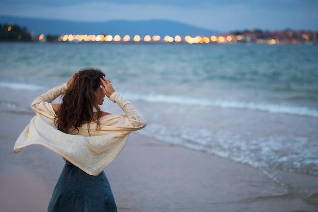 Dziewczyna patrzy na morze o zachodzie słońca
