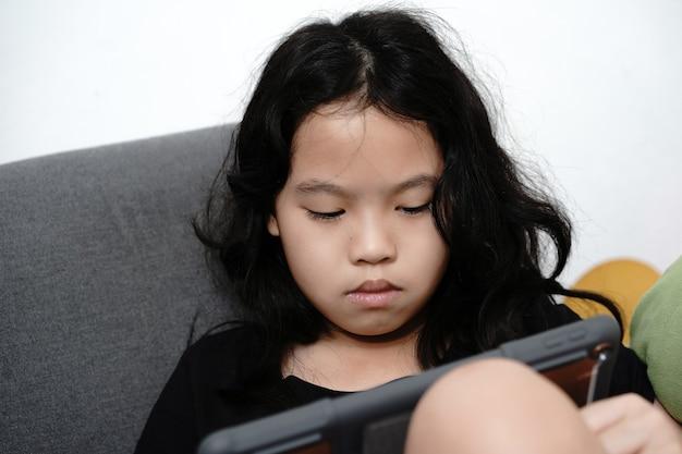 Dziewczyna patrzy na tablet do nauki online w domu w covid-19