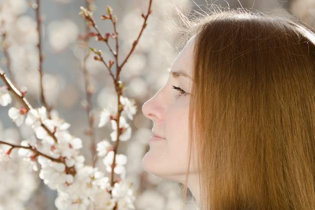 Dziewczyna patrzy w dal. kwitnąca drzewo w tle. portret