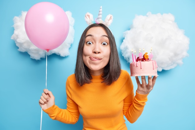 Dziewczyna patrzy z pokusą w kamerę oblizuje usta chce zjeść pyszne ciasto ma specjalną okazję świętuje 26 urodziny trzyma napompowany balon