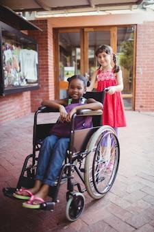 Dziewczyna pcha przyjaciela na wózku inwalidzkim w słoneczny dzień