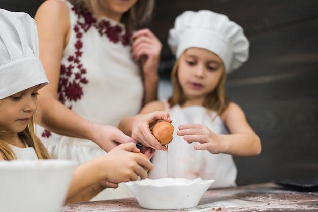 Dziewczyna pęka jajko w pucharze podczas gdy przygotowywający jedzenie