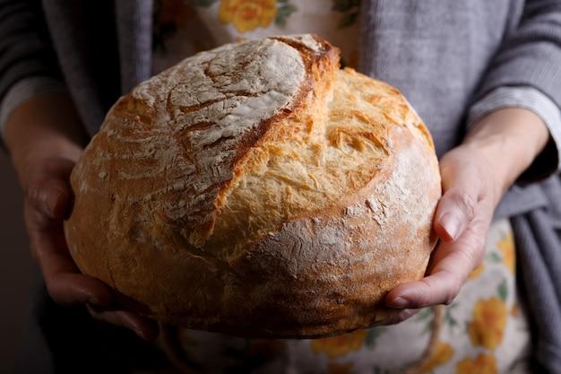 Dziewczyna piekarz trzyma świeży biały chleb