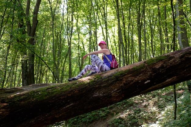 Dziewczyna piesze wędrówki w lesie, wspinaczka do dziennika