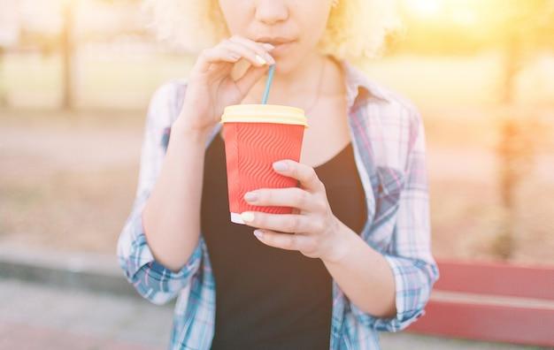 Dziewczyna pijąca kawę z papierowego kubka przez słomkę