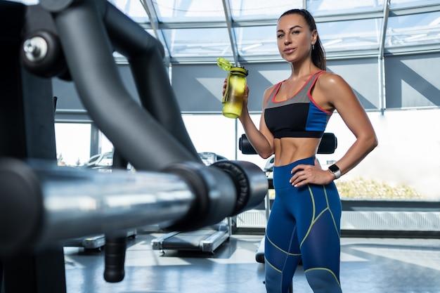 Dziewczyna pijąca wodę z butelki podczas treningu na siłowni