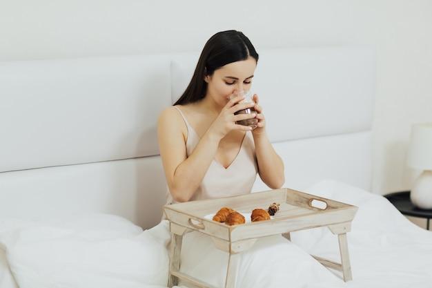 Dziewczyna pije cappuccino i je śniadanie na łóżku w godzinach porannych