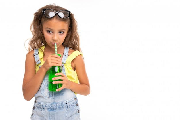 Dziewczyna pije coś ze szklanki na białym tle