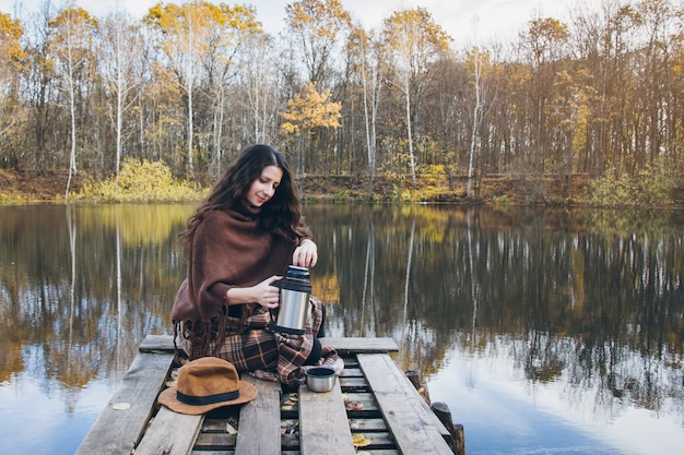 Dziewczyna pije herbaty na drewnianym moscie na jeziorze