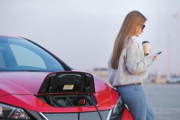 Dziewczyna pije kawę podczas korzystania ze smartfona i oczekiwania na zasilacz podłącz do pojazdów elektrycznych w celu naładowania akumulatora w samochodzie