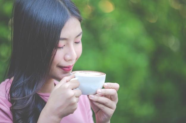 Dziewczyna pije kawę z przyjemnością w kawiarni.