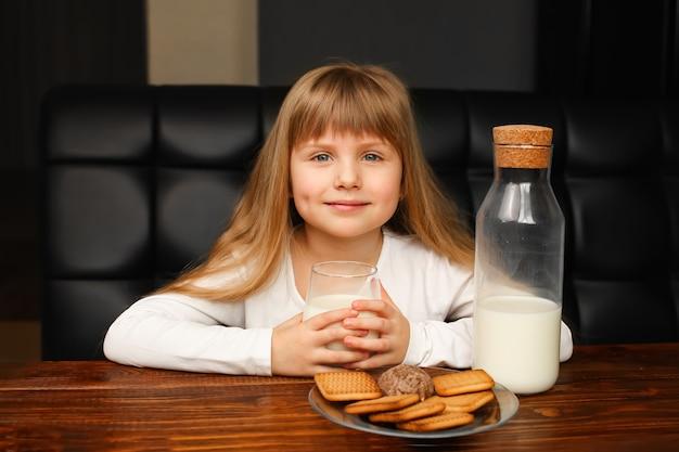 Dziewczyna pije mleko z ciasteczkami rano na śniadanie. butelka z mlekiem i szkłem, ciasteczka na talerzu na drewnianym stole, rustykalne śniadanie