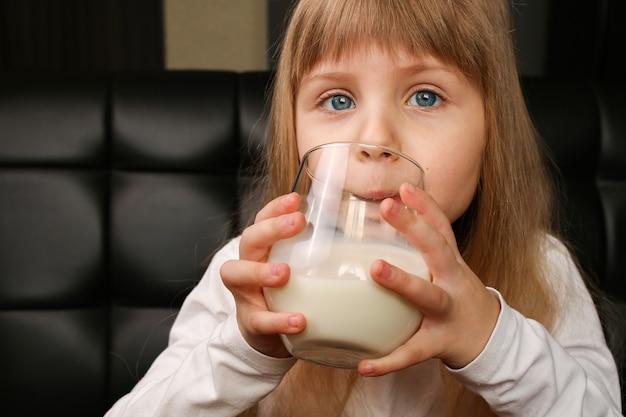 Dziewczyna pije mleko z ciasteczkami rano na śniadanie.