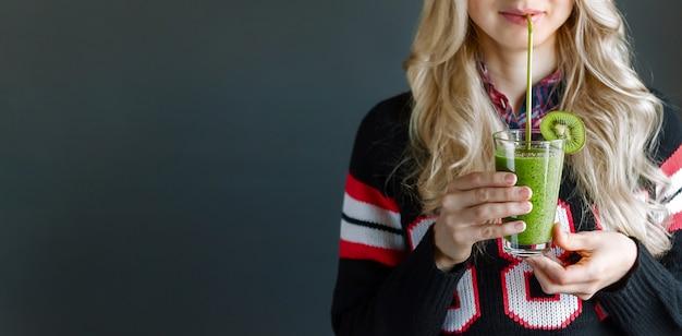 Dziewczyna pije świeżego i smakowitego zielonego smoothie.