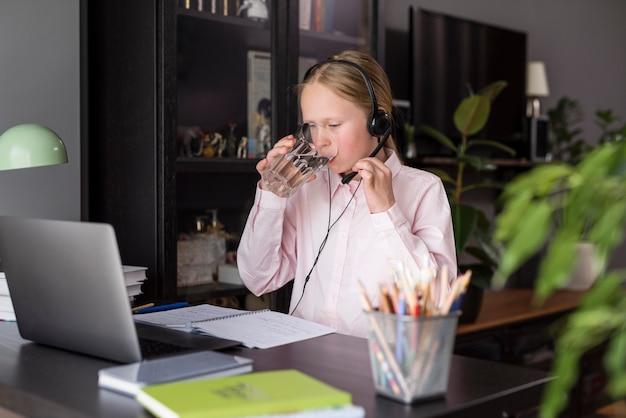 Dziewczyna pije wodę podczas zajęć online