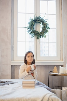 Dziewczyna pije z kubka herbaty lub innego napoju, dekoracji wnętrz na nowy rok świąteczny lub boże narodzenie