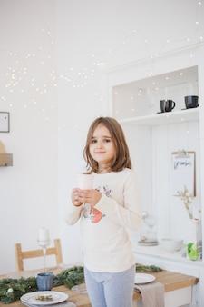 Dziewczyna pije ze szklanki soku lub napoju, girlandy i zdolne, pokój jest urządzony na boże narodzenie