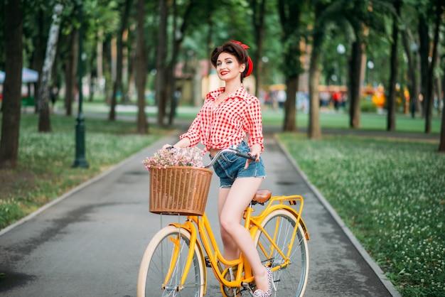 Dziewczyna pinup na retro rower z tyłu kwiatów