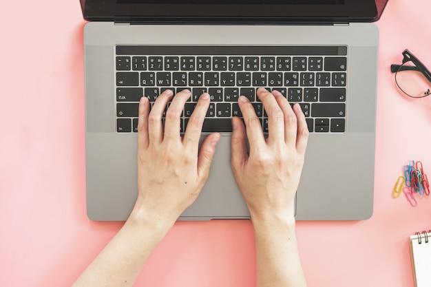 Dziewczyna pisać na laptopie w różowym pastelowym kolorowym biurze z akcesoriami