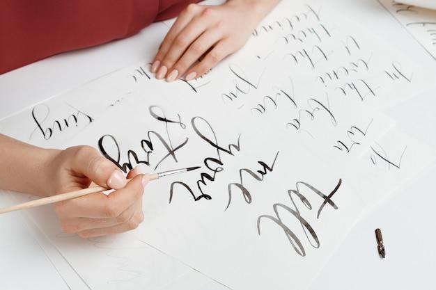 Dziewczyna pisze kaligrafii na pocztówkach. sztuki projektowania. powyżej.