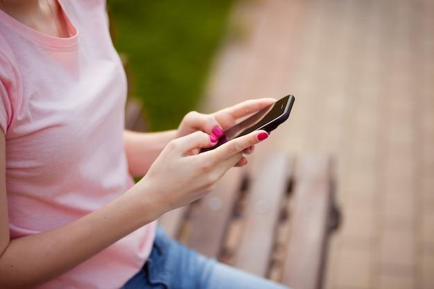 Dziewczyna pisze na telefonie siedząc w parku