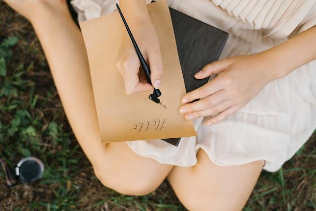 Dziewczyna pisze piórem i atramentem na liście papieru kraft. zbliżenie dłoni. romans. kaligrafia