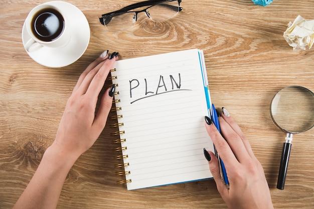 Dziewczyna pisze plany w zeszycie. pisanie planów