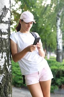 Dziewczyna pisze sms-a przez telefon. kobieta w sportowym mundurze stoi z telefonem