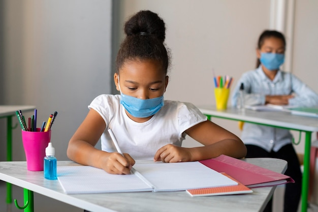 Dziewczyna pisze w klasie mając na sobie maskę medyczną
