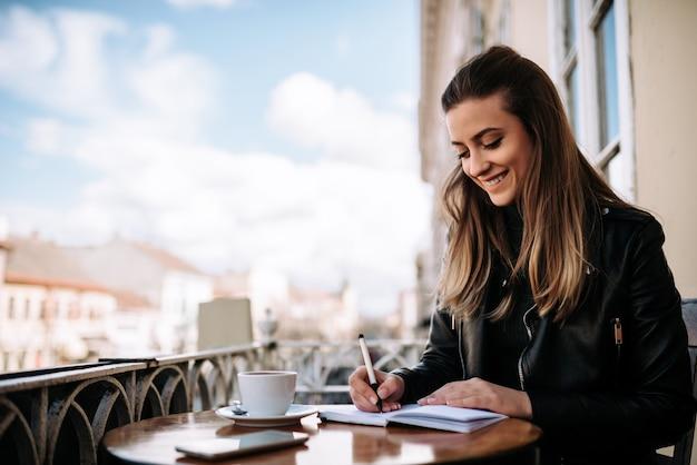 Dziewczyna pisze w notatniku podczas gdy siedzący na balkonie przy starym miasta rdzeniem.