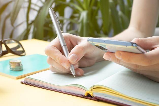 Dziewczyna pisze w notatniku, z telefonu komórkowego i filiżankę kawy