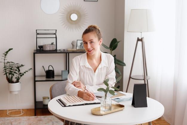 Dziewczyna pisze w pamiętniku i pracuje w domu