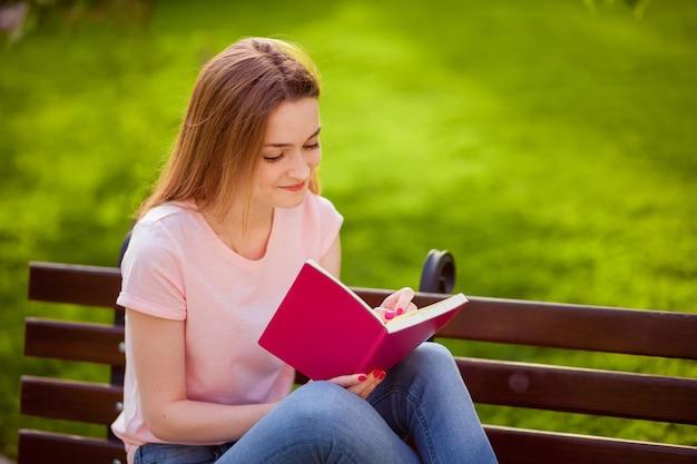Dziewczyna pisze w zeszycie, siedząc na ławce w parku