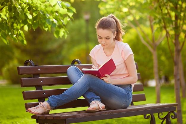 Dziewczyna Pisze W Zeszycie, Siedząc Na ławce W Parku Premium Zdjęcia