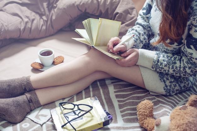 Dziewczyna pisze w zeszycie, siedząc na łóżku