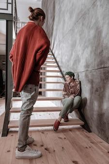 Dziewczyna płacze. blondwłosy chłopak w czerwonym sweterku wraca do domu i widzi płacz swojej dziewczyny