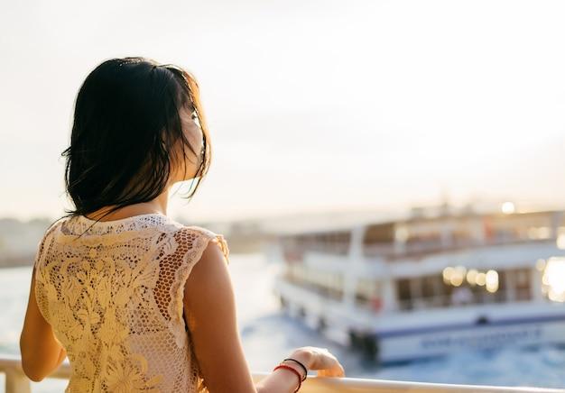 Dziewczyna płynie statkiem po wodzie o zachodzie słońca, stoi plecami, cieszy się zachodem słońca