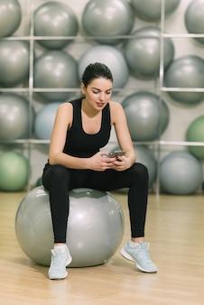 Dziewczyna po ćwiczenia piłka patrząc na telefon
