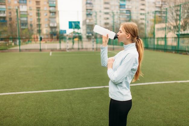 Dziewczyna po ćwiczeniach, woda pitna na boisku piłkarskim. portret pięknej dziewczyny w odzieży sportowej.