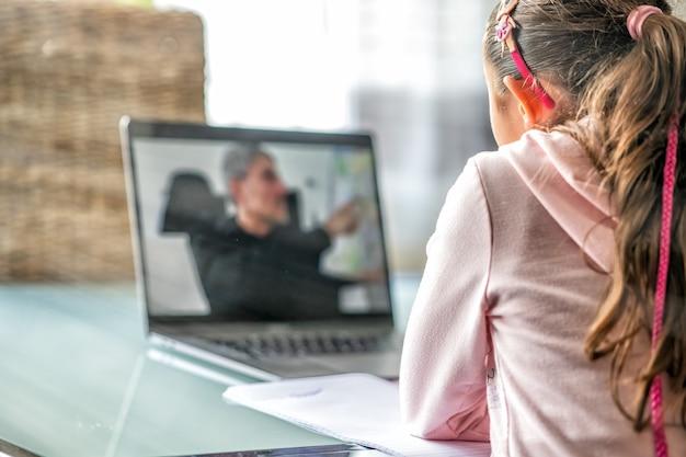 Dziewczyna po lekcji w szkole na swoim laptopie z nauczycielem płci męskiej mówiącym. szkoła w czasie pandemii