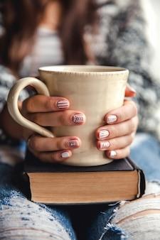 Dziewczyna po przerwie przy filiżance świeżej kawy po przeczytaniu książek lub nauce