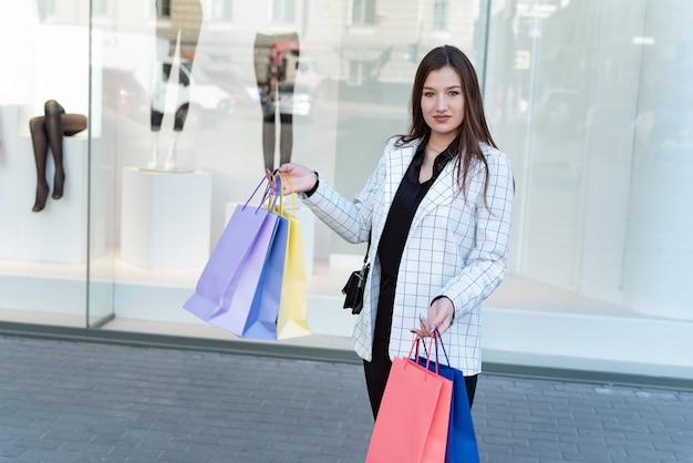 Dziewczyna po udanych zakupach przechodzi obok witryn sklepowych z różnokolorowymi torbami na zakupy