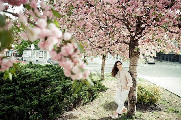 Dziewczyna pochyla się do sakury w parku