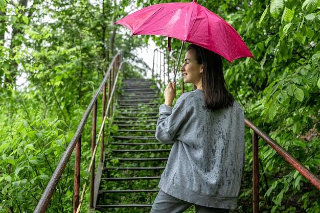 Dziewczyna pod parasolem na spacer w wiosennym lesie w deszczu.